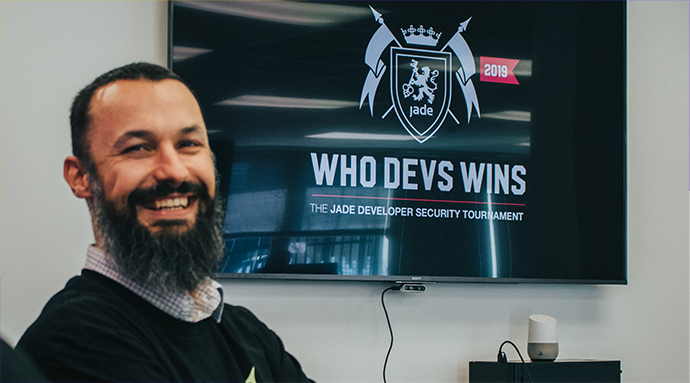 A Jade employee sitting in a meeting room infront of a TV displaying Who Devs Wins, the Jade Developer Security Tournament